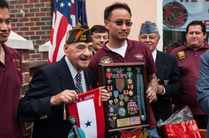"Rocco Moretto displaying the ""The Big Red One"" – 1st Infantry Division Insignia and his collection of awarded medals and ribbons, all presented by VFW Post 2348. Rocco is standing with VFW Post 2348 member Andy Cheng."