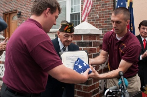 Previous VFW Post 2348 Commander, Mike Mehltretter, and Previous Quartermaster Timothy Irish, carefully handling the American flag and certificate for Rocco Moretto.