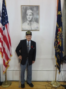 Rocco standing under the portrait that was presented to him on the 70th Anniversary of D-Day.